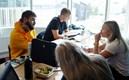Fyra studenter sitter vid ett bord och pluggar tillsammans