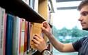 Student tar bok i biblioteket på Hälsa och Samhälle.